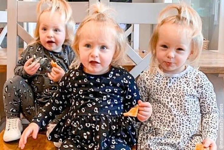 Three smiling toddlers wearing printed pyjamas eating toast