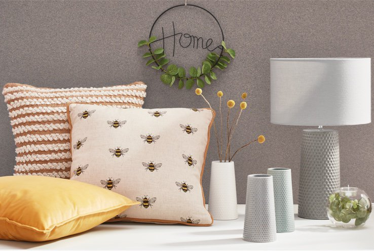Two cushions next to an assortment of vases, a grey honeycomb lamp and a glass bowl filled with an artificial plant