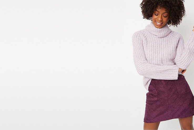 Woman wearing a lavender purple chunky knit jumper and plum purple skirt