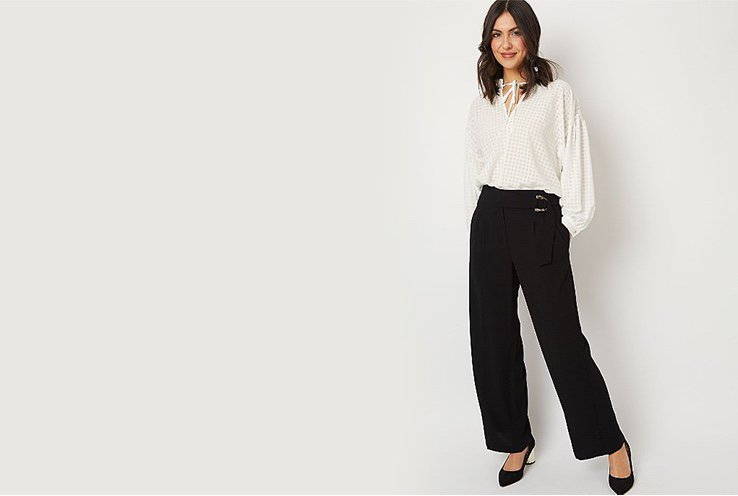 Woman wearing white grid check tie neck blouse with black belted wide leg palazzo trousers and black heels