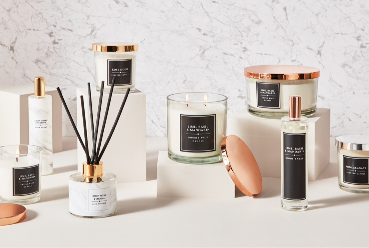 Range of scented candles, votives, reed diffusers and room sprays on or by cream-coloured blocks, all with rose gold tone lids