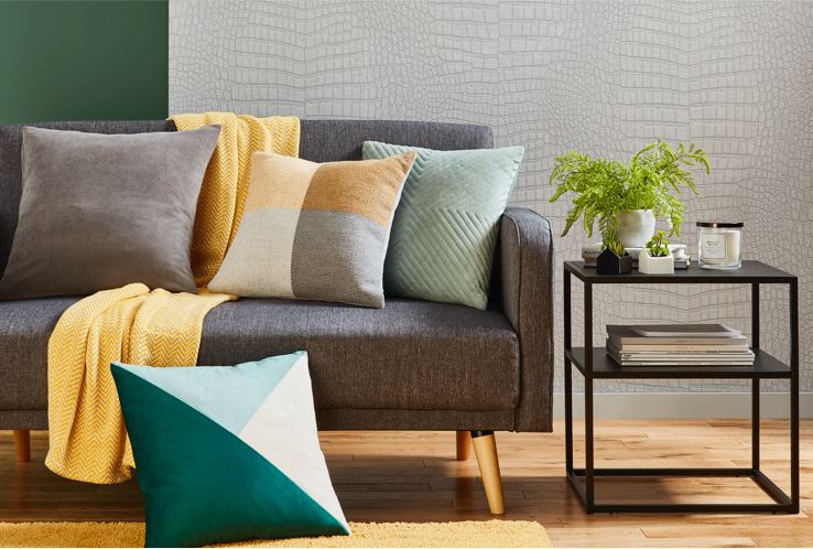 Grey sofa with an assortment of cushions, a yellow chevron throw and a side table with accessories including a candle and plant