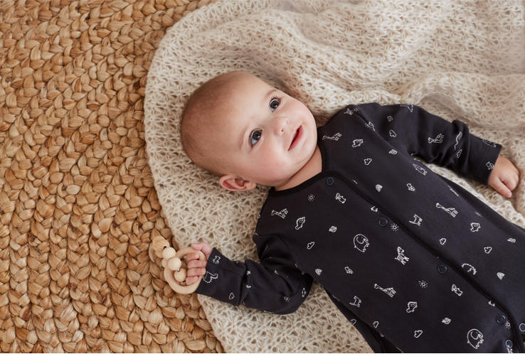 Baby wearing printed bodysuit lay on textured natural blanket