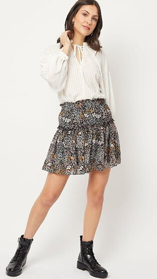 Woman wearing a dark floral print tiered mini skirt, white grid check blouse and black boots