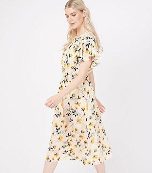 Woman wearing a cream floral print midi dress