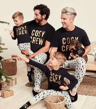Two men and two children and dog sit together smiling wearing matching black cosy crew family Christmas pyjama set.