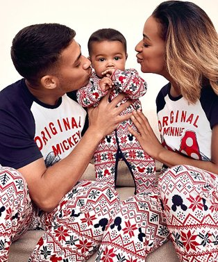 Woman and man lean into kiss cheek of baby while holding him in the air wearing matching navy and red Disney Mickey and Minnie family Christmas pyjama set.