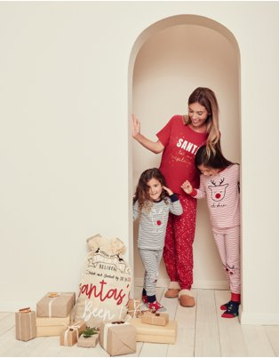 Woman and two young girls stand smiling in doorway wearing Christmas pyjamas looking at Santa sack and pile of wrapped presents.