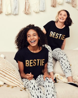 Two women sit smiling on cream sofa wearing black, white and gold bestie slogan family Christmas pyjamas.