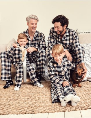 Two men, two young boys and dog sit smiling wearing black and white check print family Christmas pyjamas.