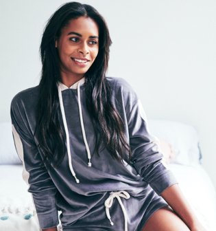 Woman poses on bed wearing grey velour hoodie and shorts.