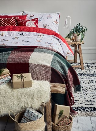 Double bed with wooden table, white lamp and plant to right hand site with multi 12 days of Christmas reversible duvet set, check print throw and wrapped presents at the bottom of the bed.