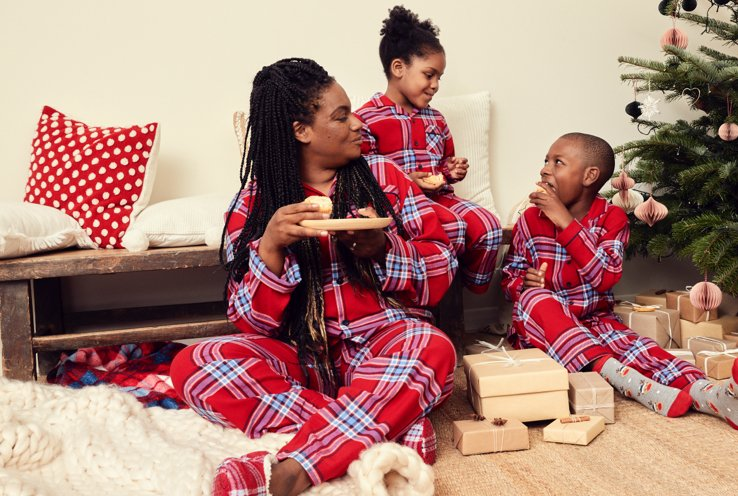 Woman, young girl and boy sit eating festive snacks wearing matching red checkered Christmas pyjamas by Christmas tree surrounded with gifts.