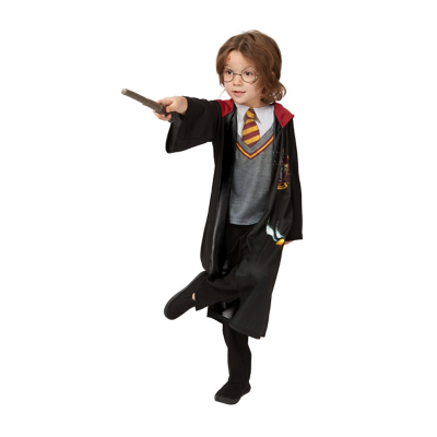 Young boy dressed in a Harry Potter wizard costume pointing out his wand