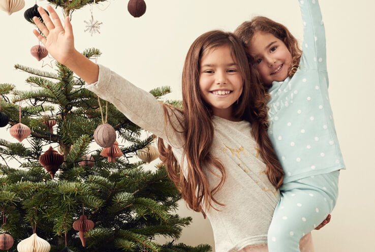 Two girls wearing pyjamas in front of a decorated Christmas tree, with the older girl holding the younger girl on her hip.