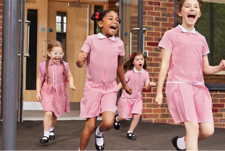 A group of school girls in red gingham dresses running outside from a classroom