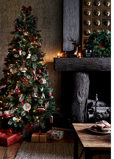 A decorated Christmas tree next to a fireplace