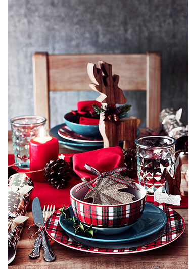 Christmas dinnerwear set laid on a wooden table