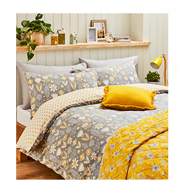 Top your bedspace off with bold yellow cushions and a throw