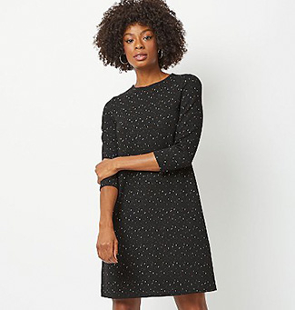 Woman wearing a black shimmering knitted dress