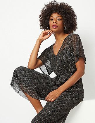 Woman wearing a black shimmering plisse jumpsuit