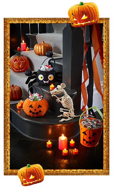 A staircase full of Halloween pumpkin baskets, candles and a skeleton rat