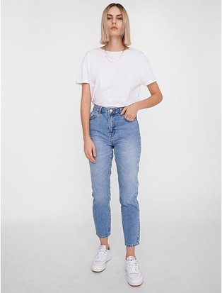 Woman poses with hand in pocket wearing white t-shirt tucked into NOISY MAY blue mid wash high waist mom jeans and white trainers.