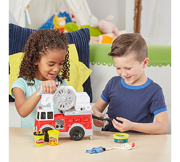 A girl and boy playing with a Play-Doh fire truck toy