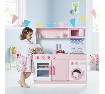 Girl enjoying pretend play in her room with a pink wooden kitchen set