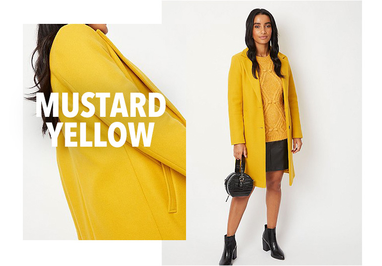 Model wearing yellow longline formal coat with a matching jumper, black skirt and boots