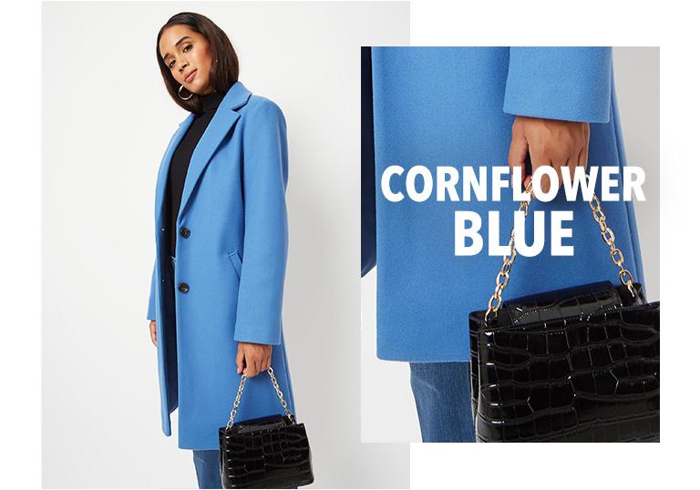 Model wearing blue longline formal coat with a black roll neck jumper and matching handbag
