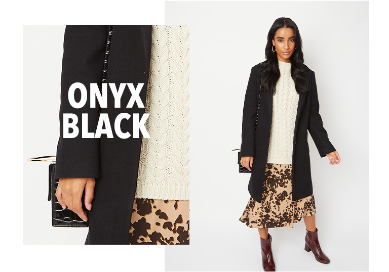 Model wearing black longline formal coat with a cream jumper, skirt and boots