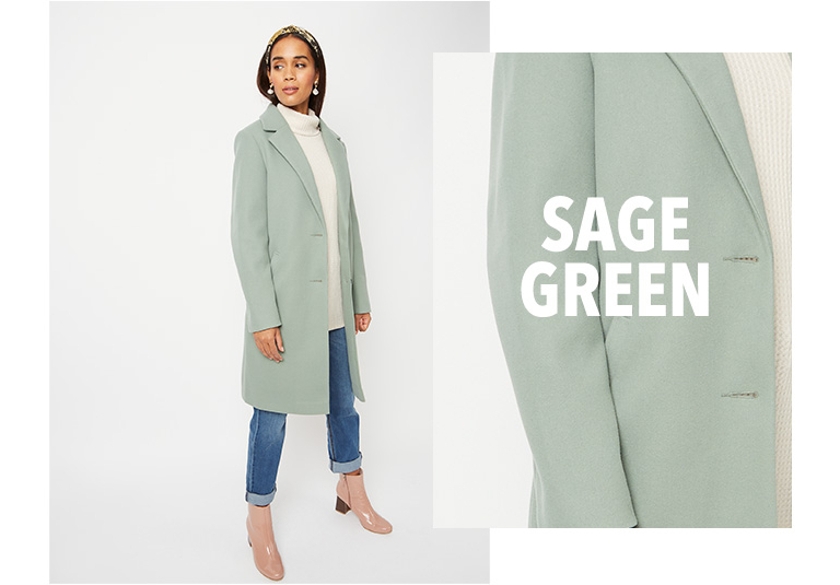 Model wearing green longline formal coat with a cream roll neck jumper, jeans and pink boots