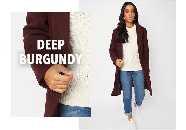 Model wearing burgundy longline formal coat with a cream jumper, jeans and white trainers
