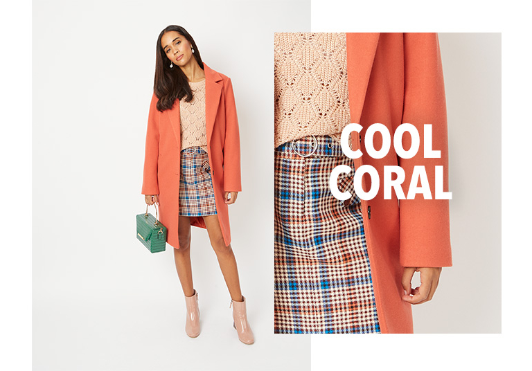 Model wearing coral longline formal coat with a pink jumper, check skirt and pink boots