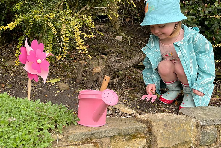 Young girl sits on wall digging with pink rake in the soil wearing a pink t-shirt and shorts under blue printed mac coat and coordinating bucket hat with greenery in the background.