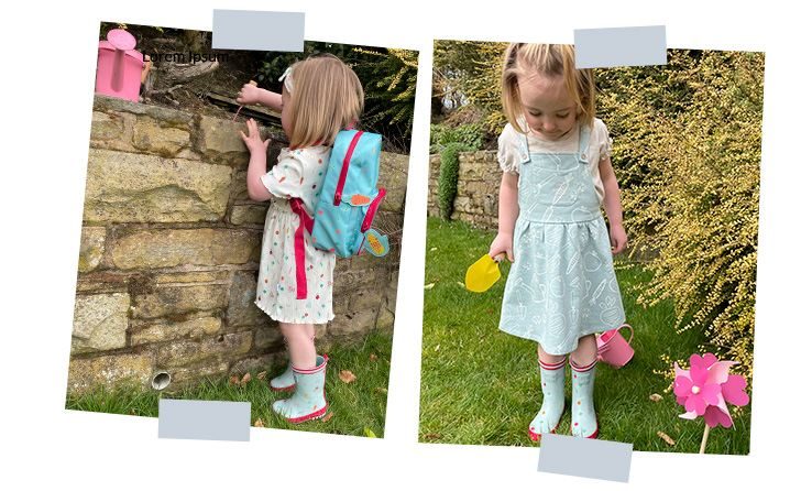 Reverse shot of young girl looking over a wall wearing a white printed dress, blue printed wellington boots and blue backpack. Young girl stands in garden looking down holding a yellow spade wearing blue printed pinafore dress and blue printed wellington boots.