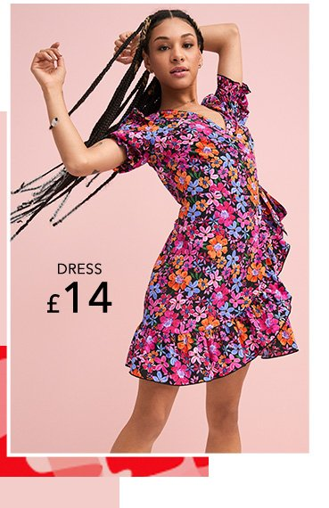 Woman poses with arms in air wearing pink floral frill trimmed wrap mini dress.