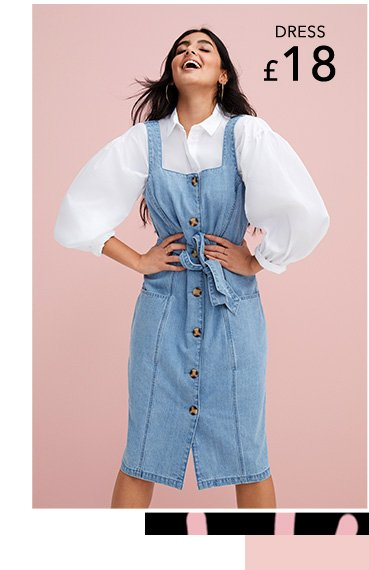Woman laughs looking up wearing white balloon sleeve button-up shirt, denim button tie front pinafore dress and gold-tone hoop earrings.