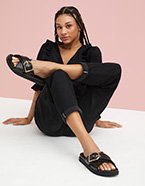Woman poses sitting on floor with hands behind her and one leg crossed over the other wearing a black blouse, black turn-up jeans and black sandals.