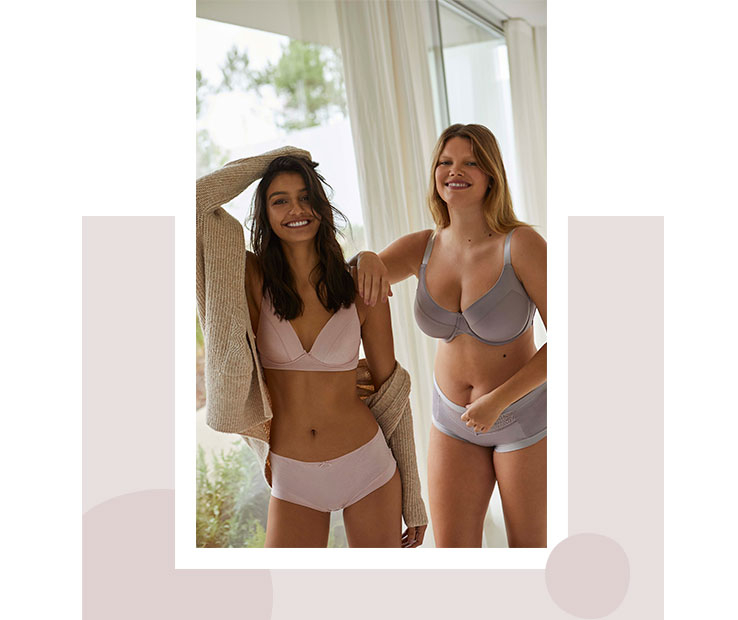 Two women, one wearing a pink bra and matching knickers, and another wearing a grey bra and matching knickers