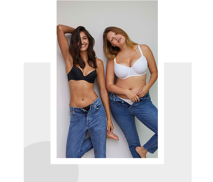 Two women, one wearing a black bra and jeans and the other wearing a white bra and jeans