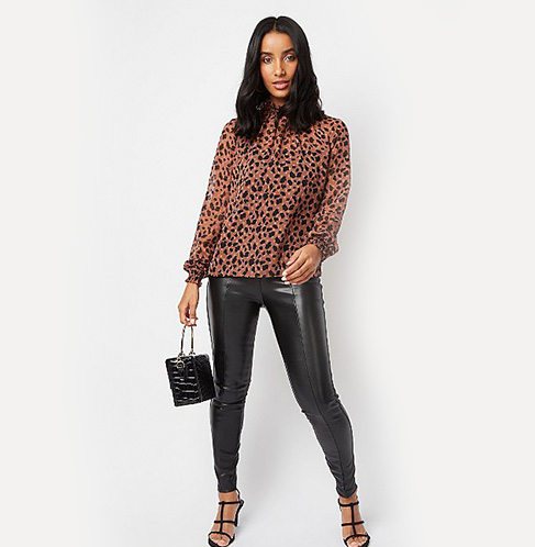 Gif of woman wearing 3 different outfits: black leather trousers and a blouse, white iridescent sequin sleeve T-Shirt and leather trousers and a tan brown ruffle front blouse