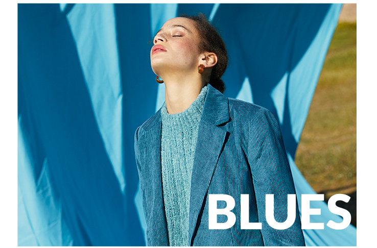 Shot of woman with her eyes closed standing in front of a blue background wearing a blue knit jumper and teal corduroy blazer