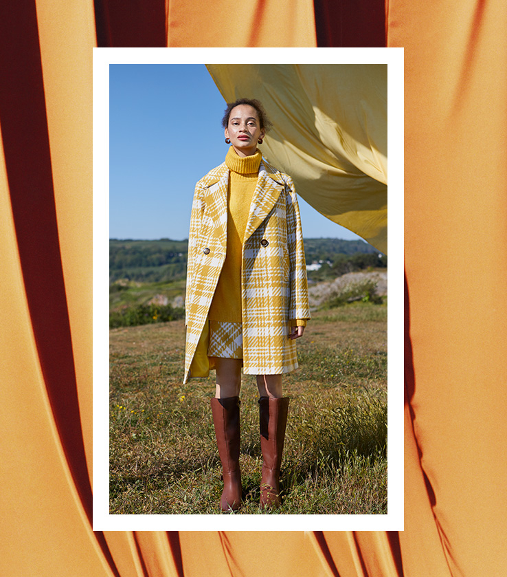 Full length shot of a woman standing in a field wearing a yellow checked skirt, roll neck jumper, matching coat and brown boots