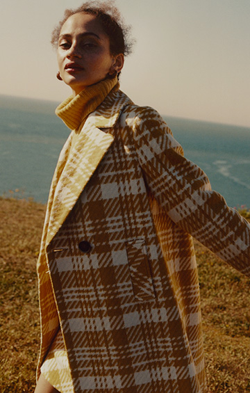 Shot of woman wearing yellow roll neck jumper and checked coat