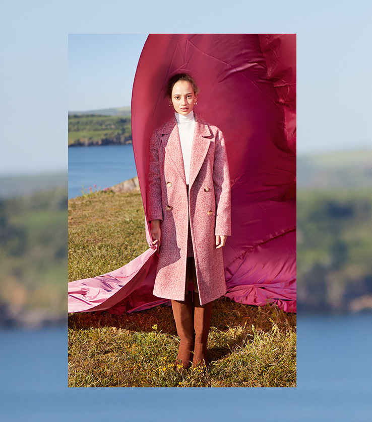 Woman wearing a white roll neck and long pink coat with brown boots