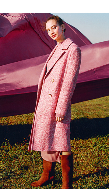 Side profile of woman wearing a long pink coat and brown boots