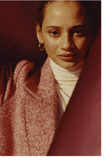 Close up shot of woman wearing a white roll neck and textured pink coat