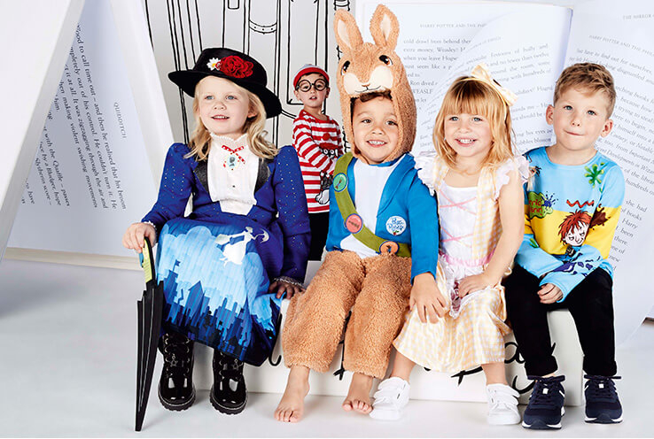 Four children sitting down, a girl wearing a Mary Poppins fancy dress costume, a boy wearing a Peter Rabbit costume, another girl wearing a Little Bo Peep costume, and another boy wearing a Horrid Henry costume and a boy standing in the distance wearing a Where's Wally? costume